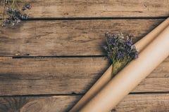 Schöne trockene Blumen und Kraftpapier vereinbarten auf die Holztischoberseite Lizenzfreie Stockbilder
