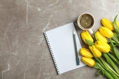 Schöne Tulpen mit Notizbüchern und Tasse Kaffee auf hellem Hintergrund stockfotos