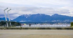 Schöne Ufergegend in Vancouver mit den Bergen von Nord-Vancouver - VANCOUVER - KANADA - 12. April 2017 Lizenzfreies Stockfoto
