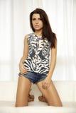 Schöne und attraktive Brunettefrau, die in Blue Jeans dre aufwirft Lizenzfreies Stockfoto