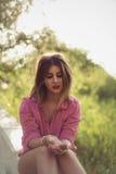 Schöne und attraktive Frau, die etwas in ihren Händen sitzt und hält Stockfotografie
