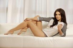 Schöne und attraktive weibliche Frau, die im grauen Hemd auf Th aufwirft Stockbild