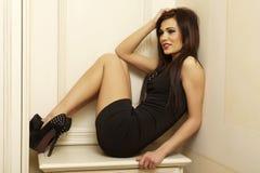 Schöne und attraktive weibliche Frau, die im schwarzen Kleid aufwirft Lizenzfreie Stockbilder
