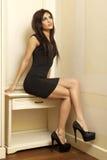 Schöne und attraktive weibliche Frau, die im schwarzen Kleid aufwirft Lizenzfreie Stockfotografie