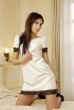 Schöne und attraktive weibliche Frau, die im weißen Kleid auf b aufwirft Stockfoto