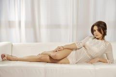 Schöne und attraktive weibliche Frau, die im weißen Kleid auf b aufwirft Stockfotos