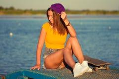Schöne und der Mode junge Frau, die mit einem Skateboard aufwirft Stockfoto