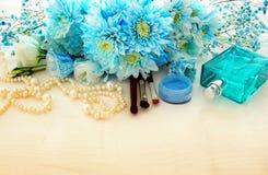 schöne und empfindliche blaue Blumenanordnung nahe bei Perlenhalskette, frischem Parfüm und Make-up stockfotos