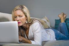 Schöne und glückliche blonde Frau frühes 40s entspannte sich zu Hause Wohnzimmer unter Verwendung des Internets auf dem arbeitend Stockbild