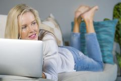 Schöne und glückliche blonde Frau frühes 40s entspannte sich zu Hause Wohnzimmer unter Verwendung des Internets auf dem arbeitend Stockfoto