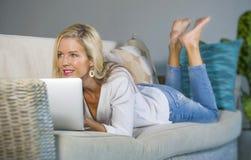 Schöne und glückliche blonde Frau frühes 40s entspannte sich zu Hause Wohnzimmer unter Verwendung des Internets auf dem arbeitend Lizenzfreies Stockfoto