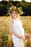 Schöne und glückliche schwangere Frau in einem weißen Kleid auf der Natur im Sommer, um die Bäume und die Blumen stockfoto