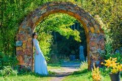 Schöne und junge Braut im weißen Kleid und im Circlet von den Blumen, die im Steinbogen aufwerfen lizenzfreies stockbild