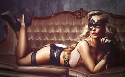Schöne und junge Frau, die in der sexy Wäsche und in venetianischem m aufwirft lizenzfreie stockbilder