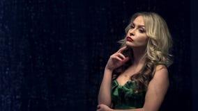Schöne und junge Frau im grünen Kleid, das vor Fenster steht und auf Regentropfen schaut stock video footage