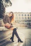 Schöne und lächelnde junge Frau in der Straße in der Stadt Lizenzfreies Stockfoto