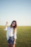 Schöne und Modefrau auf grünem Feld zeigend mit ihrer Hand Stockfotos