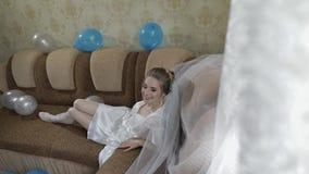 Sch?ne und reizende Braut in der Nachtkleider- und -schleierl?ge auf dem Sofa Langsame Bewegung stock footage