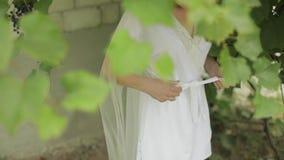 Schöne und reizende Braut im Nachtkleid und Schleier im Garten Hochzeitsmorgen stock video