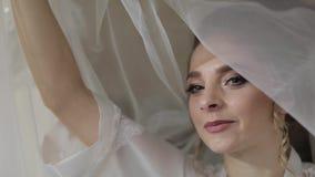 Sch?ne und reizende Braut im Nachtkleid unter enormem Schleier Hochzeitsmorgen stock footage