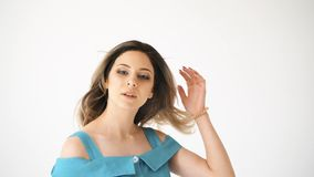 Schöne und sexy junge Frau in einem blauen Kleid mit dem dunklen Haar In Richtung der Kamera blicken, lokalisiert auf weißem Hint stock video footage