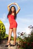 Schöne und sinnliche südamerikanische Frau bewaffnet oben mit rotem Kleid auf der Treppe im Freien Stockfotografie