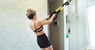 Schöne und sportliche junge Dame, die TRX-Übungen für Sitz der Körper und mehr Muskel, gesunden Lebensstil erhalten übt