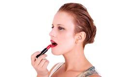 Schöne und von mittlerem Alter Frau, die Lippenstift setzt stockfotografie