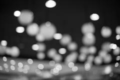 Schöne unscharfe Schwarzweiss-Lichter auf einem dunklen Hintergrund Stockfoto