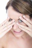 Schöne verlegene junge Frau, die durch Finger lugt Lizenzfreies Stockbild