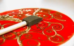 Schöne verzierte rote Glasplatte mit goldenen Stichen Muster, Werkzeugbürste, die auf die Oberseite liegt Stockfoto