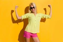Schöne vibrierende Frau biegt Muskeln und das Lächeln Lizenzfreie Stockfotografie