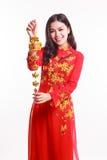Schöne vietnamesische Frau mit roter AO Dai, das glückliche Verzierung des neuen Jahres hält lizenzfreie stockbilder