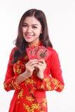 Schöne vietnamesische Frau mit roter AO Dai, das rotes Paket hält lizenzfreies stockfoto