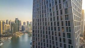 Schöne Vogelperspektive der Dubai-Jachthafenpromenade und -kanals mit sich hin- und herbewegenden Yachten und Booten vor Sonnenun stock footage