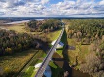 Schöne Vogelperspektive der Straßenbrücke über dem Fluss umgeben durch Wald Stockbilder
