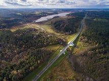 Schöne Vogelperspektive der Straßenbrücke über dem Fluss umgeben durch Wald Stockfotografie