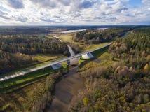 Schöne Vogelperspektive der Straßenbrücke über dem Fluss umgeben durch Wald Lizenzfreie Stockfotografie