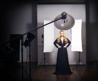 Schöne vorbildliche Aufstellung im schwarzen Kleid im Fotostudio Stockbilder