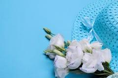 Schöne weiße Blumen Eustomablumenstrauß mit einem Hut auf einem hellen blauen Hintergrund stockbilder