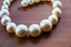 Schöne, weiße Halskette Armband hergestellt vom beadson ein Holztisch stockfotografie