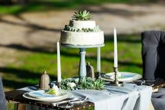 Schöne weiße Hochzeitstorte mit den Blumen im Freien Lizenzfreies Stockbild