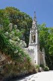 Schöne weiße Kapelle unter dem Blühen blüht im grünen Park Stockbild