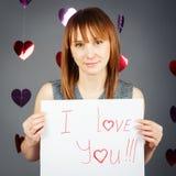Schöne weiße kaukasische blonde rote behaarte Mädchenfrau im Studio mit roten Herzen auf dem grauen Hintergrund, der ein Blatt Pa Stockbilder