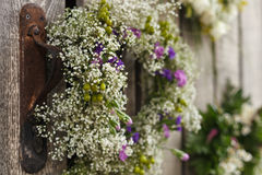 Schöne weiße und purpurrote Wildflowers in einem Kranz auf der hölzernen Wand Lizenzfreies Stockbild