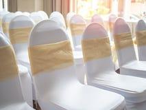 Schöne weiße und saubere Heiratsstühle verziert mit Goldbändern in der Hochzeitszeremonie stockbilder
