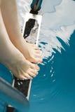 Schöne weibliche Füße auf den Schritten des Pools Stockfotografie
