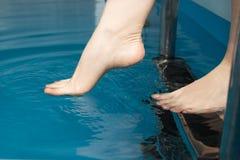 Schöne weibliche Füße auf den Schritten des Pools Stockbild