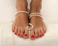 Schöne weibliche Füße mit der roten Pediküre auf Weiß und mit Perlen verziert Lizenzfreie Stockbilder