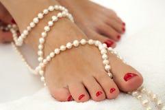 Schöne weibliche Füße mit der roten Pediküre auf Weiß und mit Perlen verziert Stockbild